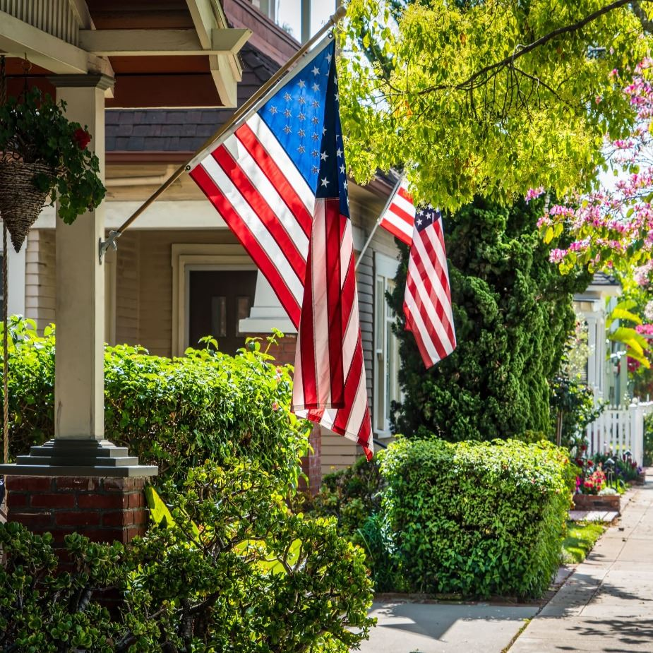 American Flag displayed on a house in a neighborhood