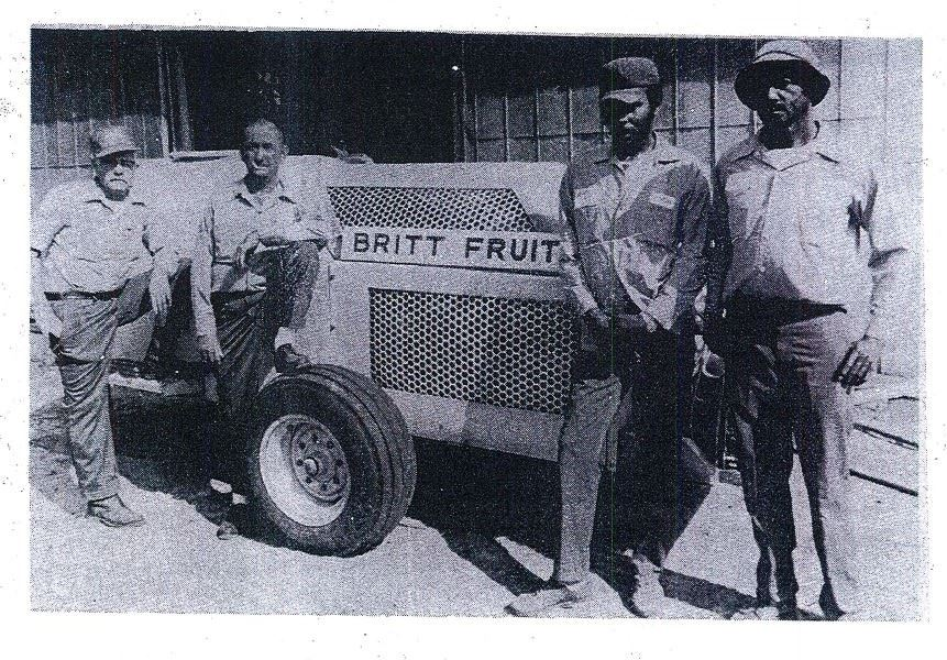 Photo of two white and two black men in front of a tractor